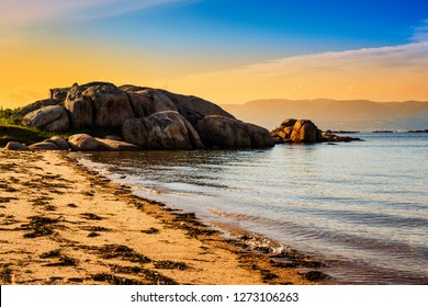 Coastal rocks on the beginning of Aguiuncho beach in Arousa Island at golden sunset