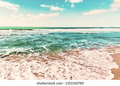 Coastal scene with waves in vivid colors on a sandy beach. Dubai