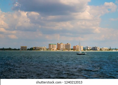 Coastal scenery of Fort Myers beach at Estero Island in Florida, view from boat through the sea waters to the beach with beachfront hotel buildings