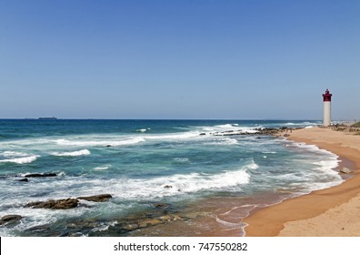 Coastal seascape against red and white lighthouse and blue sky in Umhlanga near Durban, South Africa