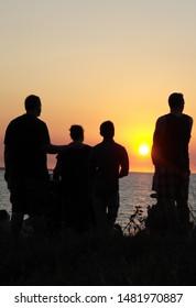 Coastal seaside sunset people silhouette