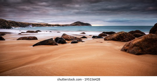 Coastal sunset with soft waves washing over the beach and rocks