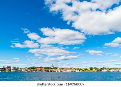 The coastal town of Vastervik, Sweden, on a sunny and fine summer morning. White clouds in the sky and a calm Baltic sea in the foreground. Logos removed.