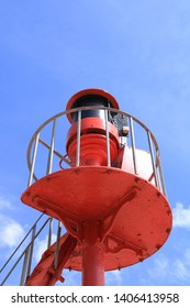 A coastal viewing platform with a warning light for shipping. Painted a bright coastal red against a deep blue summer sky. Could be used as a coastal home interior picture.