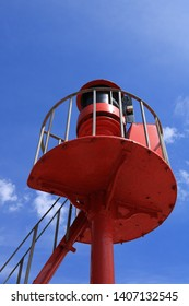 A coastal viewing platform with a warning light for shipping. Painted a bright coastal red against a deep blue summer sky. Could be used as a coastal home interior picture. Deliberately underexposed.