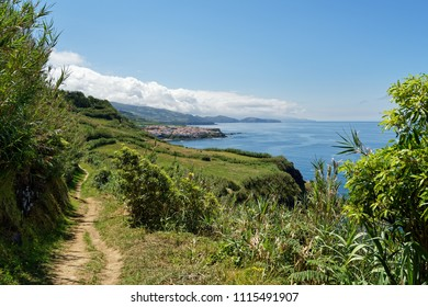 Coastal walk on the Azores island of Sao Miguel in sunny weather, the view follows the trail past pastures to a village and mountains with clouds - Location: Azores, island of Sao Miguel