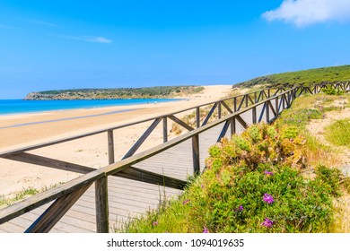 Coastal walkway along blue sea on white sand Bolonia beach, Andalusia, Spain