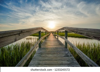 coastal waters with a very long wooden boardwalk pier in the center during a colorful summer sunset under an expressive sky with reflections in the water and marsh grass in the foreground