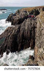 Coasteering horizontal climbing along sea cliffs on the Isle of Anglesey