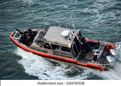 Coastguard patrol boat racing alongside a cruise ship as it exits Port Everglades,Fort Lauderdale,Florida on 22 December 2018.