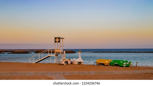 Coastguard station and pedal boats on the beach with red. It is the island of Fuerteventura- Caleta de Fuste. It's in the Canary Islands. There is beautiful sunset.
