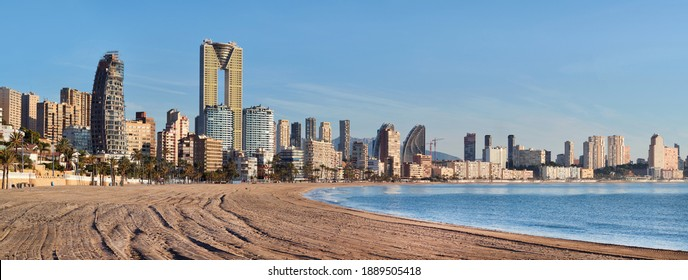 Coastline of Benidorm sandy beach view. Spanish famous touristic resort city. Modern skyscrapers, Mediterranean Sea. Province of Alicante, Costa Blanca, Spain