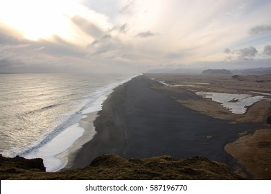 The coastline of black volcanic beach between the ocean and the land from Cape Dyrholaey, Vik, South Iceland in the evening sunlight.