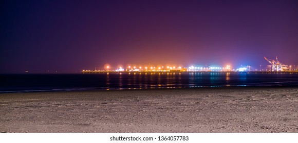 the coastline of Blankenberge beach lighted by night, colorful lights on the industry terrain in the distance