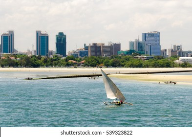 Coastline of Dar Es Salaam. A fishing boat is sailing along the beach towards the huge drainage pipe extending in to the ocean. The skyline with skyscrapers are in the background
