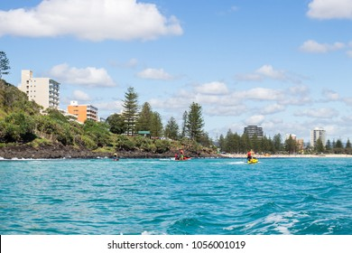 Coastline of the Gold Coast, Australia on a beautiful sunny day with blue crystal clear turquoise water viewed from a boat over the Palm Beach reef and Burleigh Headland with jet skis in the distance