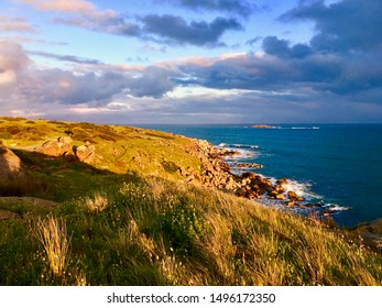 Coastline with grassy hill at sunset with clouds and blue ocean