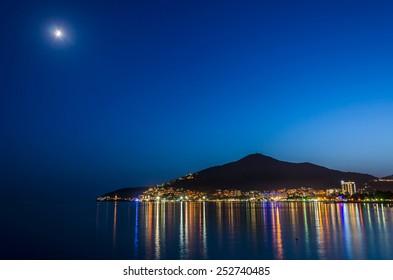 Coastline of illuminated Budva in Montenegro under moonlight. Landscape of european town near the sea.