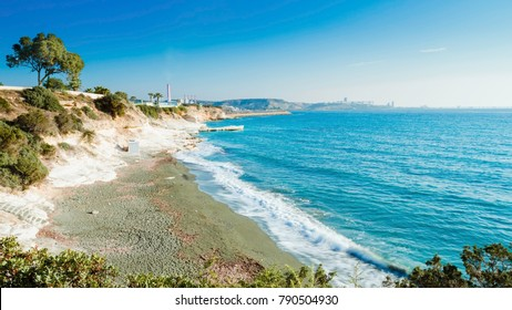 The coastline and landmark big white chalk rock at Governor's beach, Limassol, Cyprus. Steep stone cliffs and deep blue sea waves crushing in coves and dark sand next to Vasilikos power station.