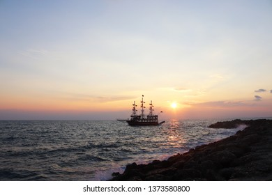 Coastline Landscape in Side, Antalya, Turkey. White foam of a sea wave. Beautiful Sunset with sailing ship in the sea.