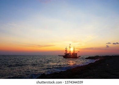 Coastline Landscape in Side, Antalya, Turkey. Beautiful Sunset with sailing ship in the sea. White foam of a sea wave.