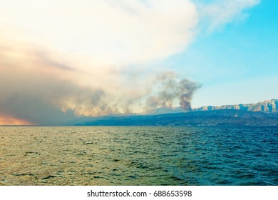 Coastline of Mediterranean sea with pillars of smoke over burning forests