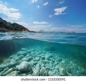 Coastline near Javea town with the cape San Antonio in background and rocks underwater, split view above and below water surface, Mediterranean sea, Costa Blanca, Alicante,