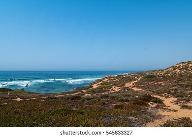 The coastline in portugal showing the ocean, cliffs, beach, and waves