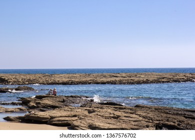 Coastline with sedimentary rocks and tide pools at the northern Cyprus with two persons sitting for sun bathe