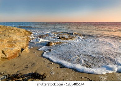 Coastline at sunset and foam of wave on a beach at Damgan, a commune in the Morbihan department of Brittany in north-western France.