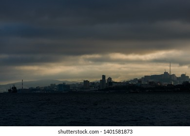 The coastline of Vladivostok from the sea. Vladivostok in inclement weather. The sea facade of Vladivostok.