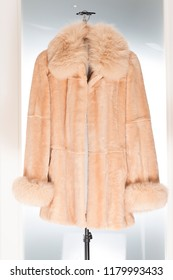 Coat belonging to a collection of fur coats, vison etc Very expensive, brand and haute couture On white background hanging on hangers