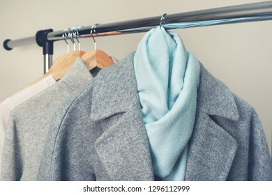 coat, blue scarf and warm clothes on a hanger close-up