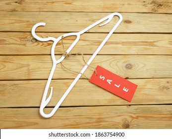 coat hanger and blank red price tag on wooden background, clothing sales concept, closeup