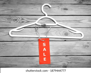 coat hanger and blank red price tag on wooden background, clothing sales, closeup