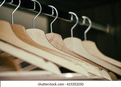 Coat hangers/Several empty coat hangers seen in perspective inside a home closet.