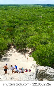 Coba, Quintana Roo / Mexico - August 2018: A group of tourists going down the stairs of the Coba pyramid