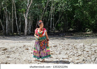 Coba ruins, Quintana Roo, Mexico - November 17, 2016: native Mexican mayan young brunette woman with long hair dressed in traditional colorful Mexican dress clothes outfit. Coba archaeological site.