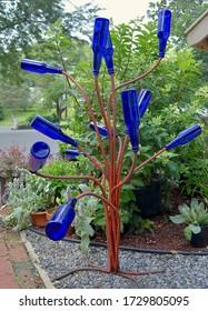 Cobalt blue glass bottles on a handmade rebar bottle tree.