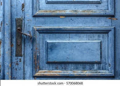 Cobalt blue painted aged worn wooden door with black wrought iron latch