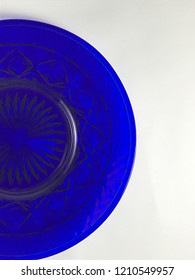 Cobalt blue plate with pattern against a white table