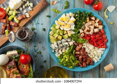 Cobb salad.  Main-dish American garden salad typically made with chopped salad greens , tomato, crisp bacon, grilled chicken breast, hard-boiled eggs, avocado, chives, Roquefort cheese. Top view.