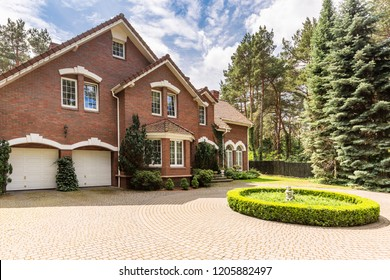 Cobbled circle driveway with green shrubs decoration in front of a traditional red brick English house with steep roof and white windows.