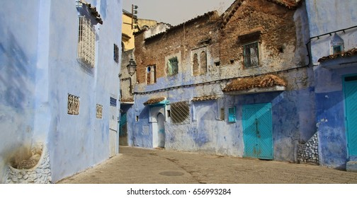 A cobbled laneway with blue hued buildings in the ancient town of Chefchaouen, Morocco.