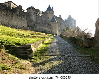 Cobbled path with two people approaching the old walled city at Carcassonne, France