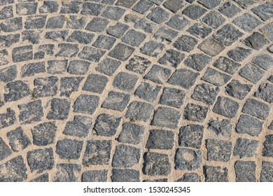 Cobbled road close-up. Pedestrian paving in street. Paved, detail. Brown texture of a paving stone track on a sand.