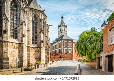 Cobbled street with church and belfry tower in Walloon city center of Mons, Hainaut, Belgium.