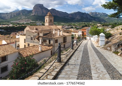 Cobbled street to church of Polop de Marina with rocky mountainrange, Costa Blanca, Spain