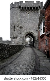 cobbled street leading up to Lewes Castle Gate, Lewes, East Sussex, the cobbled street and lewes castle gate are ib black and white and the historic building on the left is toned brown