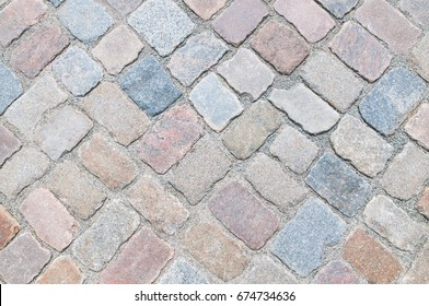 Cobbled surface with paving stones in different shades - top view; Natural stone pavement; Exterior floor covering.
